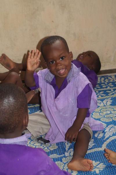 Volontär på barnhem - Liten pojke ler och vinkar till kameran vid barnhem i Togo