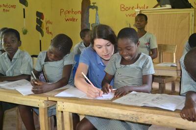 Volontär undervisar ung flicka i engelska vid undervisningsprojetk i Ghana.