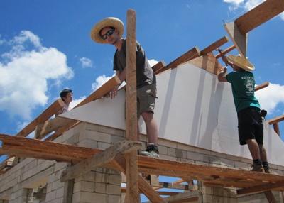 Två volontärer från Projects Abroad på en byggnadsställning installerar takbjälkar på ett hus vid byggprojektet på Filippinerna.