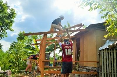 Volontär håller på att konstruera en husram för ett nybygge vid byggprojektet på Filippinerna