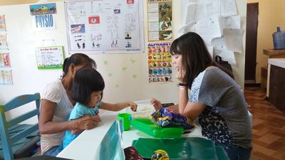 En fysioterapivolontär arbetar med en patient på rehabiliteringscentret där Projects Abroad kommet att ha sitt korta byggprojekt på Filippinerna