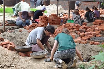 Kvinnlig volontär lägger tegel vid byggnation av skola vid projektet för katstrofhjälp i Nepal