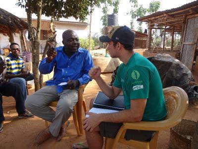 Volontär diskuterar landfrågor med lokal jordbrukare, vid