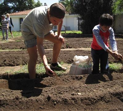 Volunteer and child grow organic vegetables on and organic farm with Projects Abroad
