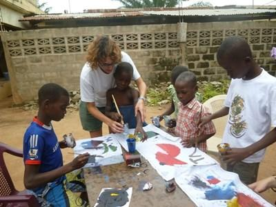 Volunteer on the Farming project paints outside with children in Togo with Projects Abroad