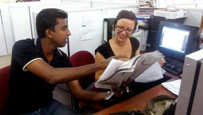 A local journalist assists an intern at a print house in Sri Lanka