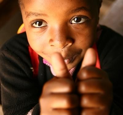 Child gives a thumbs up at a volunteer project in Tanzania