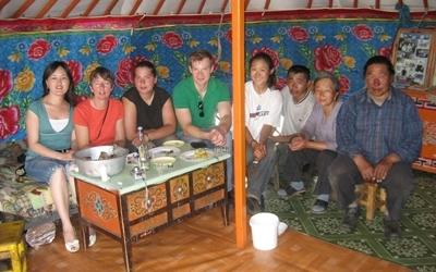 Volunteers and nomads sit in a tent on the Culture & Community project in Mongolia, Asia