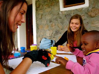 Kvinnlig volontär använder handdocka i terapiarbetet med en liten flicka.