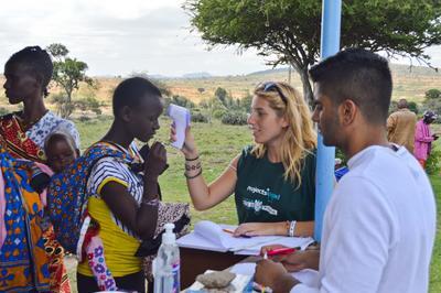 Volontär tar temperaturen på patient vid fältarbete i Kenya.