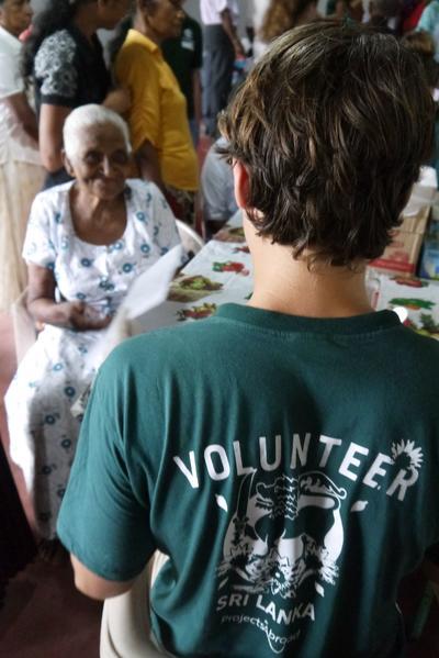 Volontär delar ut medicin till äldre patient under fältarbete vid farmaciprojektet på Sri Lanka.