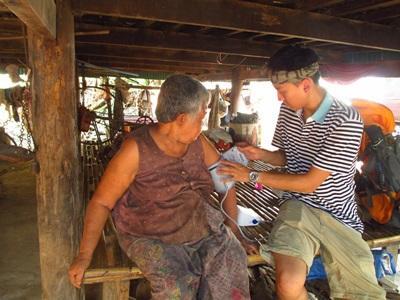 Volontär från Projects Abroad mäter blodtryck på patient under fältarbete i Kambodja