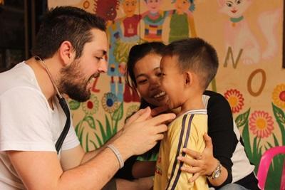Volontär från Projects Abroad undersöker en pojkes tänder under fältarbete i Kambodja