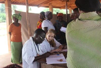 Läkare tillsammans med volontär arbetar vid outreach inom ramarna för folkhälsoprojektet i Togo.