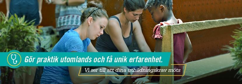 Kvinnlig volontär vi folkhälsoprojekt i Ghana lägger om ett sår på en liten flickas knä