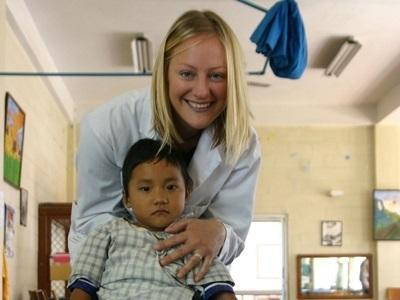 Medicine volunteer with a child in a hospital in Nepal