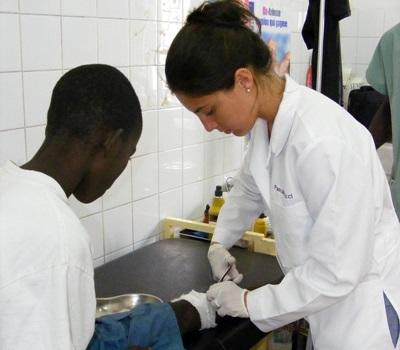 Gap year intern working with a child in a clinic on the Medicine project in Senegal
