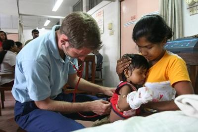 Volunteer checking the heartbeat of a child in a clinic in Sri Lanka