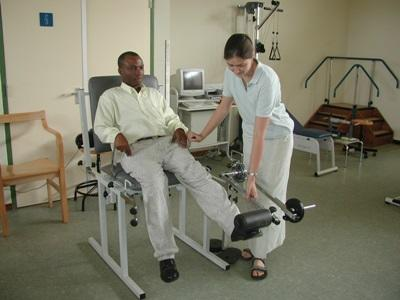 Physical Therapy intern assists a man with a leg problem at a clinic in Ghana