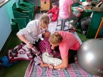 Volunteers work with disabled children in a clinic on the Physical Therapy project in Nepal