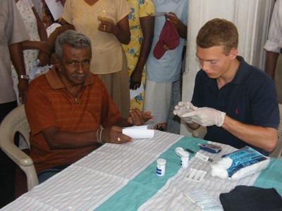 Volunteer treats elderly man on a physical therapy project in Sri Lanka, Asia