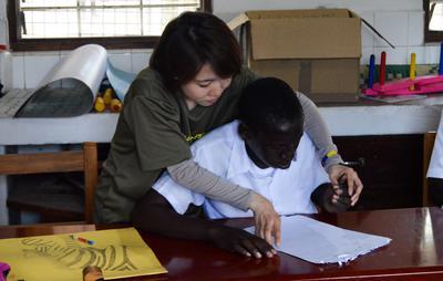 Kvinnlig sjukgymnastikvolontär hjälper patient att rita.