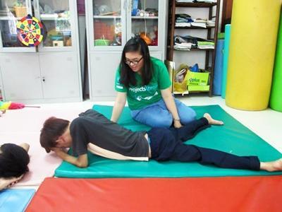 Volontär ger ung patient sjukgymnastikbehandling vid projekt i Vietnam