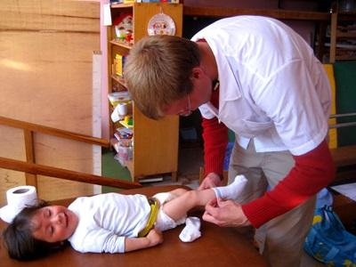 Volunteer on the Nursing project dressing a child in a clinic in Peru