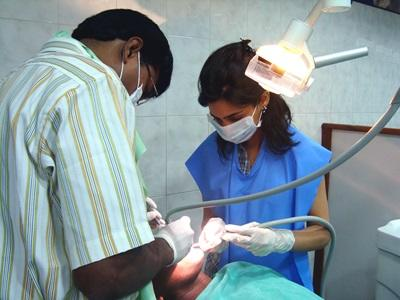A dentist is helped by his assistant during a routine dental checkup in India