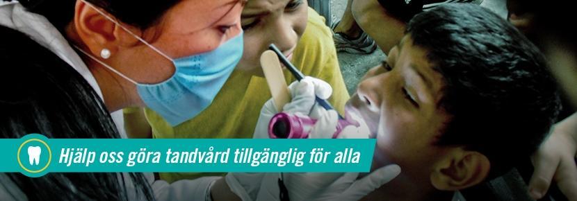 Kvinnlig volontär vid tandvårdsprojekt undersöker ung pojke