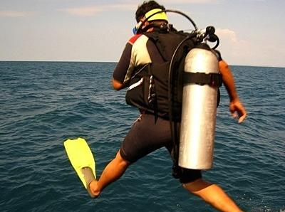 Volunteer jumps in the ocean with oxygen tank for a dive on the Conservation project in Cambodia