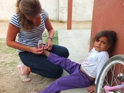 An Argentinian child sits while a volunteer puts on shoes for her at a Care placement