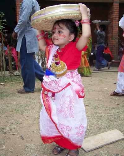 Liten flicka i traditionella kläder bärandes en flätat korg