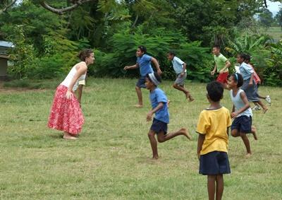 Volunteer playing tag with a group of children on a childcare educational project in Fiji