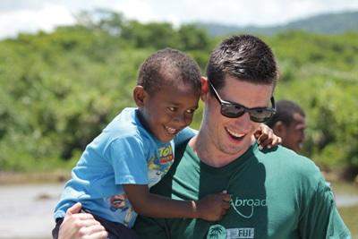 A Fijian child is carried by a Projects Abroad volunteer