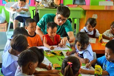 A volunteer helps children with an activity at a care center in the Philippines