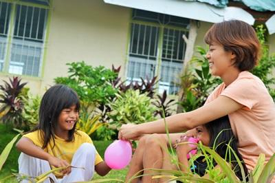 Volunteer and child play with water balloons at a care center on the Care project in the Philippines with Projects Abroad