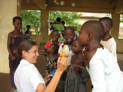 Volunteer on a care project in Ghana blows bubbles with the girls from the care center
