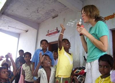 Volunteer blows bubbles with kdis at a care center in India with Projects Abroad