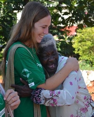 Volontär från Projects Abroad omfamnar äldra dam vid outreach-projekt på Jamaica.