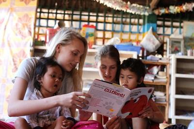 Två volontärer vid omsorgsprojektet i Kambodja läser sagor för barnen.