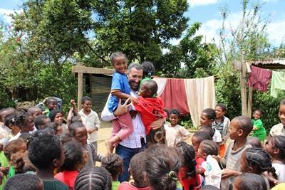 Manlig volontär från Projects Abroads omsorgsprojekt på Madagaskar är omringad av lekande barn