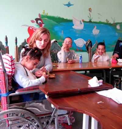 Volunteer works with disabled children in a special needs care center in Morocco