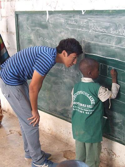 Volunteer helps student with a class activity on the chalkboard in a classroom in Senegal