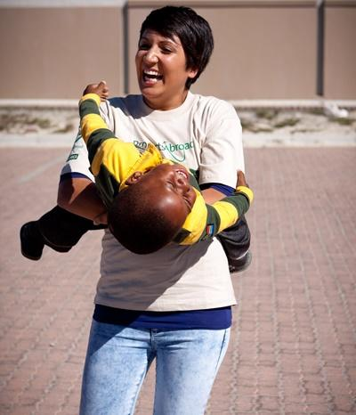 Volunteer holding a young boy at a care center in South Africa on the Care project