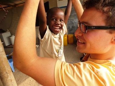 A Togolese child smiles during playtime with a Projects Abroad volunteer