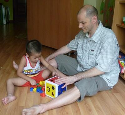 Professional volunteer plays with children with blocks in a care center in Vietnam