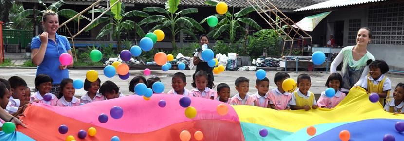 Två volontärer leker med barn