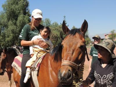 Volontär assisterar vid behandling av liten flicka vid projektet för hästterapi i Sydafrika