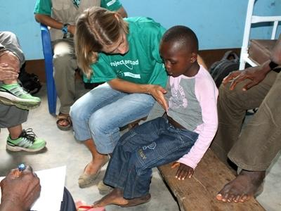 A local child receives help from a Projects Abroad volunteer in Togo, Africa.